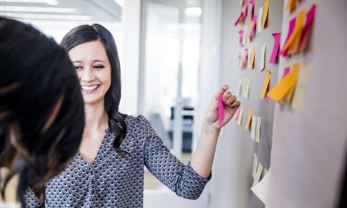 An attractive young Asian businesswoman leading a brainstorming session by putting post it notes on the wall